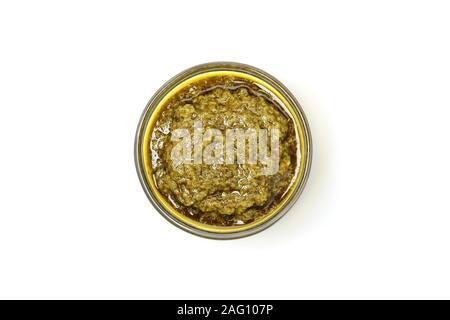 Tasty pesto sauce in bowl isolated on white background - Stock Photo