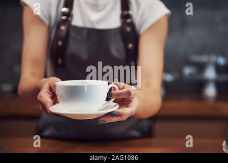 Take your order. Holds white cup of fresh drink. Young female cafe worker indoors. Conception of business and service - Stock Photo