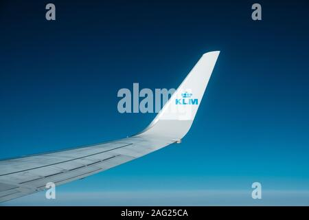 Amsterdam, Netherland - November, 2019: Airplane wing and company brand logo of KLM airlines isolated on blue sky - Stock Photo