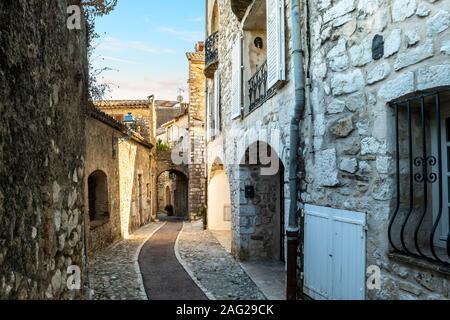 A narrow, cobbled stone alley through the hilltop medieval city of Saint Paul de Vence, France at dusk.