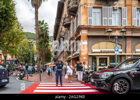 A female policewoman directs traffic at a red and white crosswalk in the urban center of Ventimiglia, on the Italian Riviera. - Stock Photo