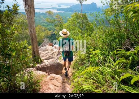 Traveler hikes along rocky path in tropical forest with stunning landscape & sea far below on horizon, in Krabi, Thailand. Khao Ngon Nak Nature Trail - Stock Photo