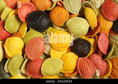 Colorful durum wheat orecchiette pasta with special ingredients: dried carrot, red beet, spinaches, basil, tomatoes, turmeric powder and squid ink. - Stock Photo