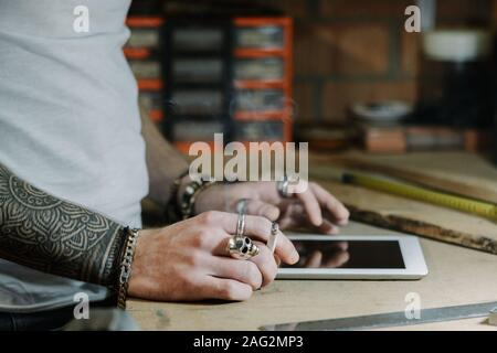 Craftsman artist using a tablet and checking some ideas for a new designer wooden product in his home workshop while smoking a cigarette - Stock Photo