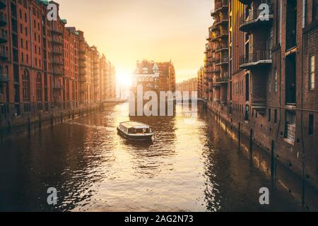 Hamburg warehouse district in golgen hour sunset lit. Water castle palace and tourist visting boat trip in river. Old warehouse port, Germany, Europe