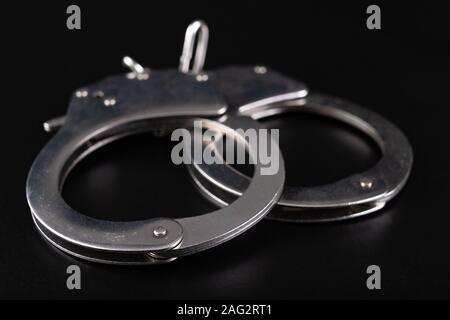 Nickel-plated handcuffs on a black table. Accessories for special services and police. Dark background. - Stock Photo