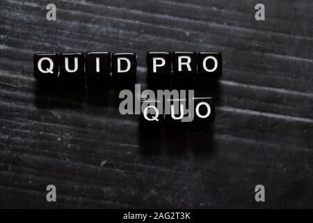 Quid Pro Quo in Latin on wooden cubes. On table background - Stock Photo