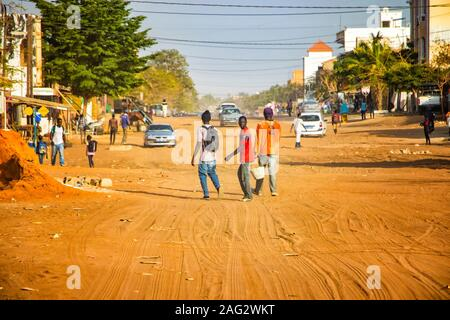 Mbour, SENEGAL - APR 26, 2019: Unidentified Senegalese men are walking down a dusty road in the middle of the city. There's a car on the sand. It is - Stock Photo