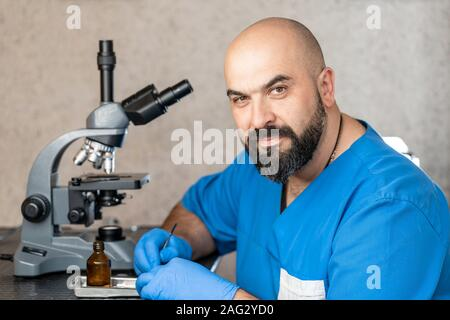 Male laboratory assistant examining biomaterial samples in a microscope. - Stock Photo
