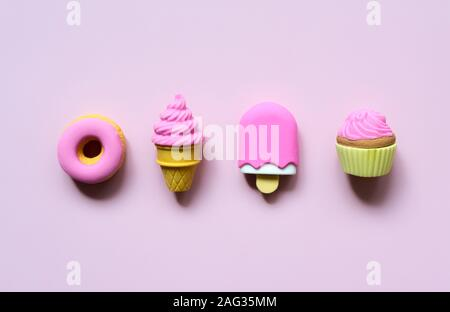Different toy sweets in miniature with shadows close-up on a soft pink color background. - Stock Photo