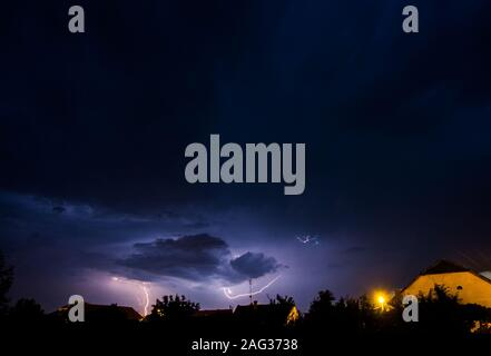 Beautiful shot of a light storm in the dark sky over a country scenery - Stock Photo