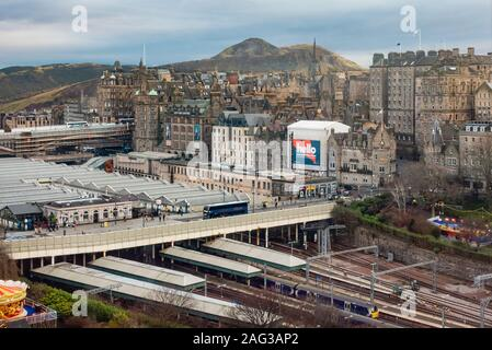 An elevated view of part of Edinburgh, looking over Waverley Station, Waverley Bridge and part of the Old Town, with Arthur's seat in the background. - Stock Photo