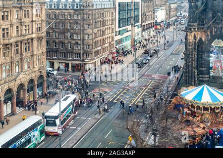 Elevated view of part of Princes Street, the most famous street in central Edinburgh. Busses and taxis can be seen, as well as many pedestrians. Carousels and market stalls can be seen as part of Edinburgh's Christmas. Jenners department store can be seen, and at the other side of South St David Street, Monsoon, Accessorize and other shops. The bottom of the Scott Monument is top left of the photo. - Stock Photo