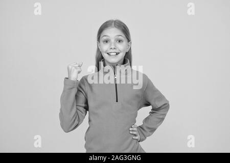 Happiness is key to success. Happy girl keep fist raised with success on yellow background. Little child enjoy success in something. Best practice and success. - Stock Photo