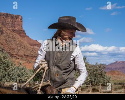 A young, attractive working cowgirl wrangler on her horse on a ranch near Moab, Utah.  Behind her are the sandstone cliffs of the canyon of the Colora