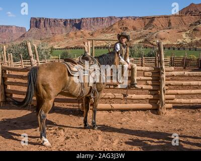 A young attractive working cowgirl wrangler sits on a wood rail fence by her horse on a ranch near Moab, Utah.