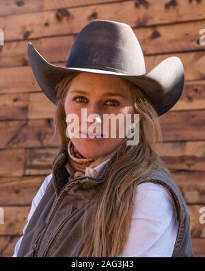 A young attractive working cowgirl wrangler poses on her horse on a ranch near Moab, Utah.