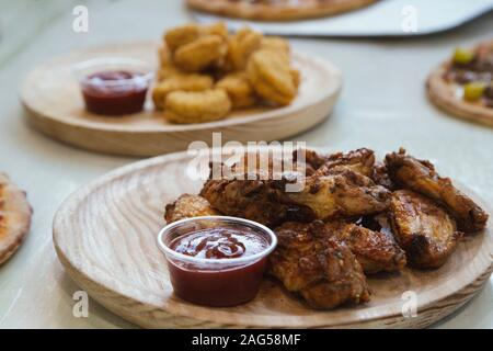 Close-up of chicken wings cap with ketchup sauce on wooden plate. - Stock Photo