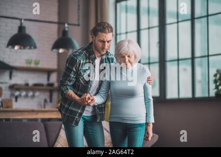 Elderly mom. Young man in jeans supporting his ill mom - Stock Photo