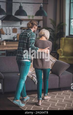 Sons support. Young man in jeans supporting his mom - Stock Photo