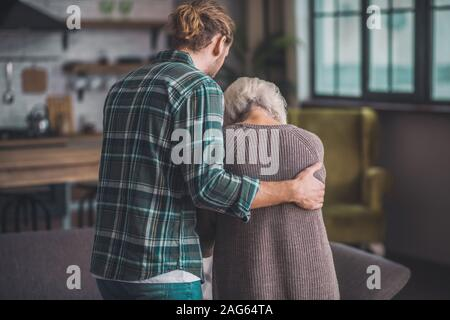 Strong hand. Young man in jeans supporting the old lady - Stock Photo