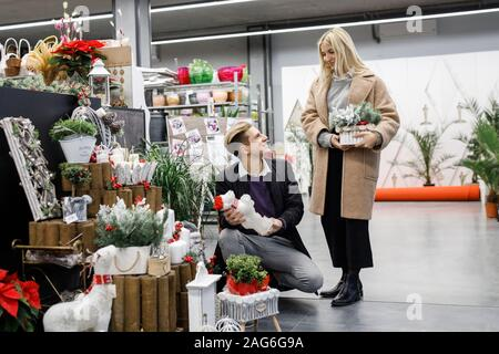 Young man with woman shopping presents in store in time before the winter holidays. Beautiful couple buys gifts for family and friends - Stock Photo