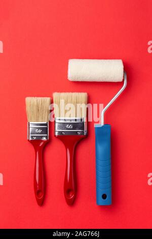 Paint roller and two brushes on red background. Top view minimal styled repair concept.