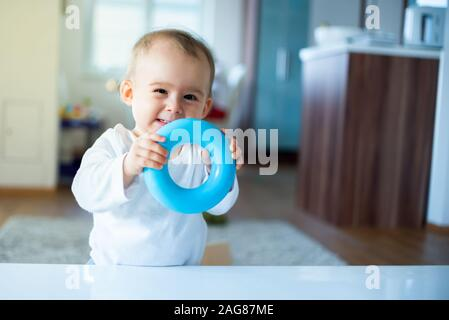 Caucasian baby girl standing next to table with blue torus in hands and laughing