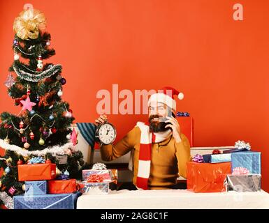 Santa holds cellphone and alarm clock. Gadgets and celebration concept. Man with beard and happy face sends greetings on New Year. Santa Claus talks on mobile phone near fir tree on red background. - Stock Photo