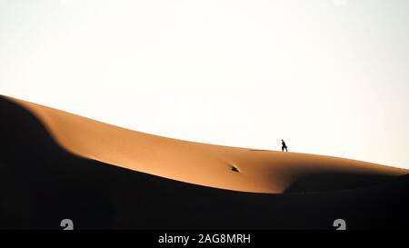 the man walking on the sand dune in lut desert