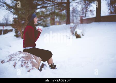 Dark-haired female with a red jacket and a skirt sitting on a stone and praying in a snowy area