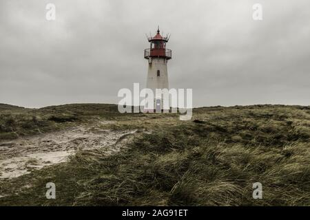 A low angle shot of the Lighthouse List East at Sylt, Germany under the storm clouds - Stock Photo