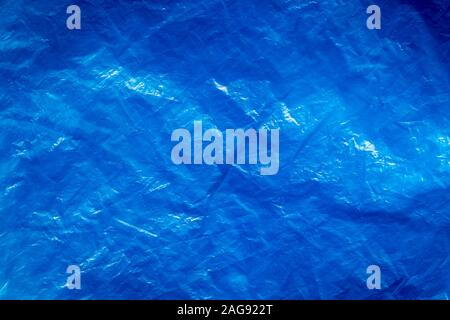 Texture of crumpled blue plastic trash bag. Abstract background for design with copy space.