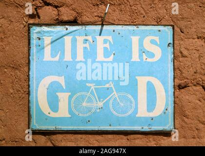Message of LIFE IS GOOD on the blue board hanging on the rough wall - Stock Photo