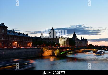 La Conciergerie and the Sainte Chapelle spire from Seine River bridge at sunset. Paris, France. - Stock Photo
