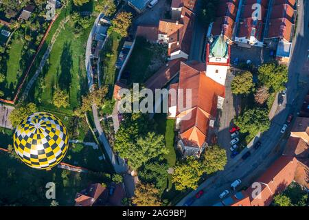 An aerial shot of an air balloon flying over a cityscape during daytime - Stock Photo