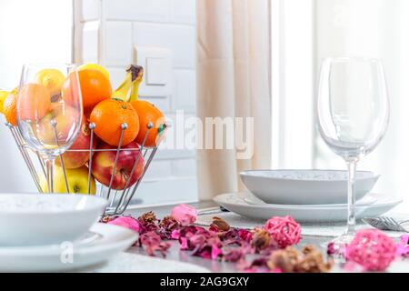 A selective focus shot of a modern table setting with flower petals, fruit and beautiful silverware - Stock Photo