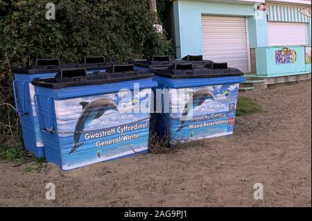Four large rubbish and recycling bins on the beach with the Ceredigion Dolphin logo - Stock Photo