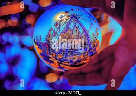 A selective focus shot of a crystal ball reflecting a ride from a theme park - Stock Photo