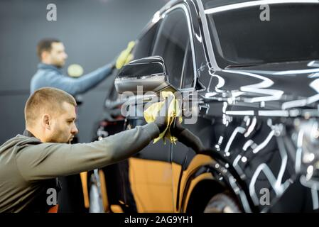 Car service workers wiping vehicle body with microfiber, examining glossy coating after the polishing procedure. Professional car detailing and maintenance concept