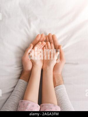 Father and daughter holding something in hands, open palms - Stock Photo