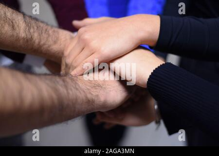 College Students Teamwork Stacking Hand Concept. Close up of young people putting their hands together. Friends with stack of hands showing unity and - Stock Photo