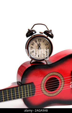 Children's six-string guitar and old retro alarm clock on white background. Stock Photo