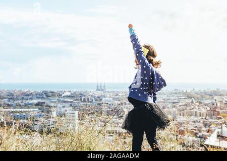side view of a little child girl posing powerful with her fist in the air disguised as a superhero with homemade costume in front of a cityscape, imag