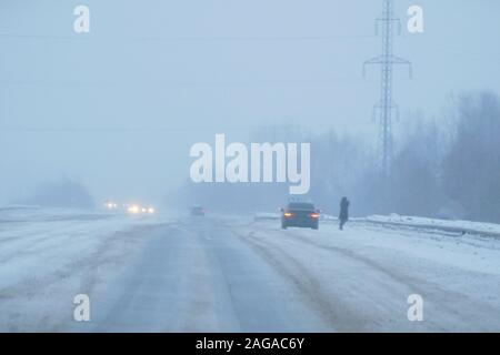 The car in the falling snow and fog is at the roadside in the evening. A man standing beside it. Visible burning lights of an oncoming cars - Stock Photo