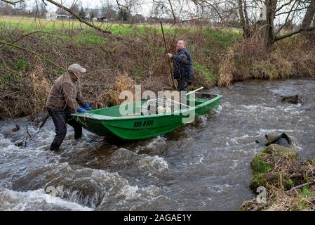Zerbst, Saxony-Anhalt, Germany. 18th Dec 2019. Jens Winterheuser (l) and Robert Wolf from the Institute for Inland Fisheries Potsdam-Sacrow search for spawning salmon with an electric fishing gear. A total of 143,500 young salmon and 90,300 sea trout hatchlings have been released into the Nuthe near Zerbst in the past ten years. The fish migrate to the Atlantic and return to spawn in the Nuthe after a few years. Credit: Mattis Kaminer/Alamy Live News - Stock Photo