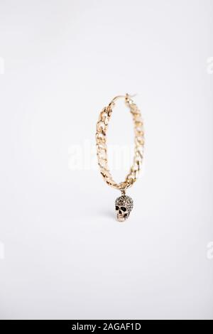 A closeup shot of a chain bracelet with a skull charm on white background - Stock Photo