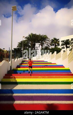 A young boy in a Spanish national soccer team shirt, running down multi coloured steps near Playa de la Torrecilla, Nerja, Malaga Province, Spain - Stock Photo