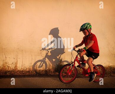 A young boy in a Spanish national soccer team shirt, riding a bike at sunset on a Campo road, Frigiliana, Malaga Province, Andalusia, Spain - Stock Photo