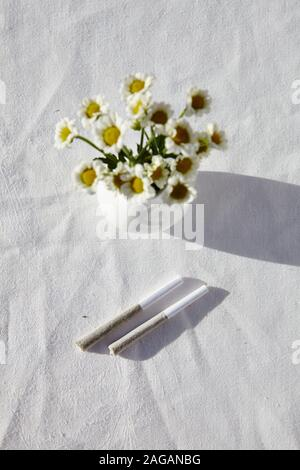 A vertical overhead shot of a vase of chamomiles on a table with a white tablecloth - Stock Photo